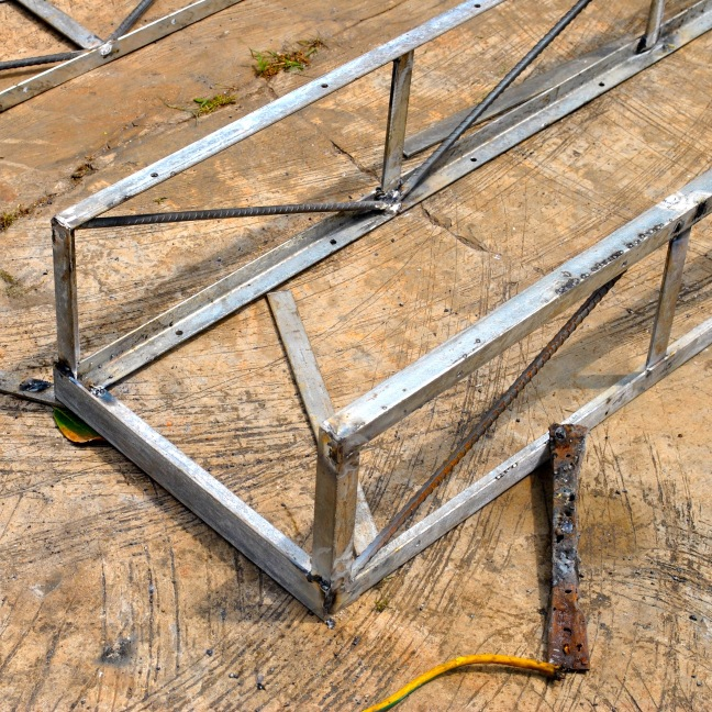 on flat and level ground surface, weld pair of 2d trusses together with 1-1/2in angle bar at top and bottom corners.